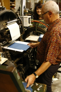 Poet Jennifer Liston watches Charles Zammit binding and stamping her second poetry collection